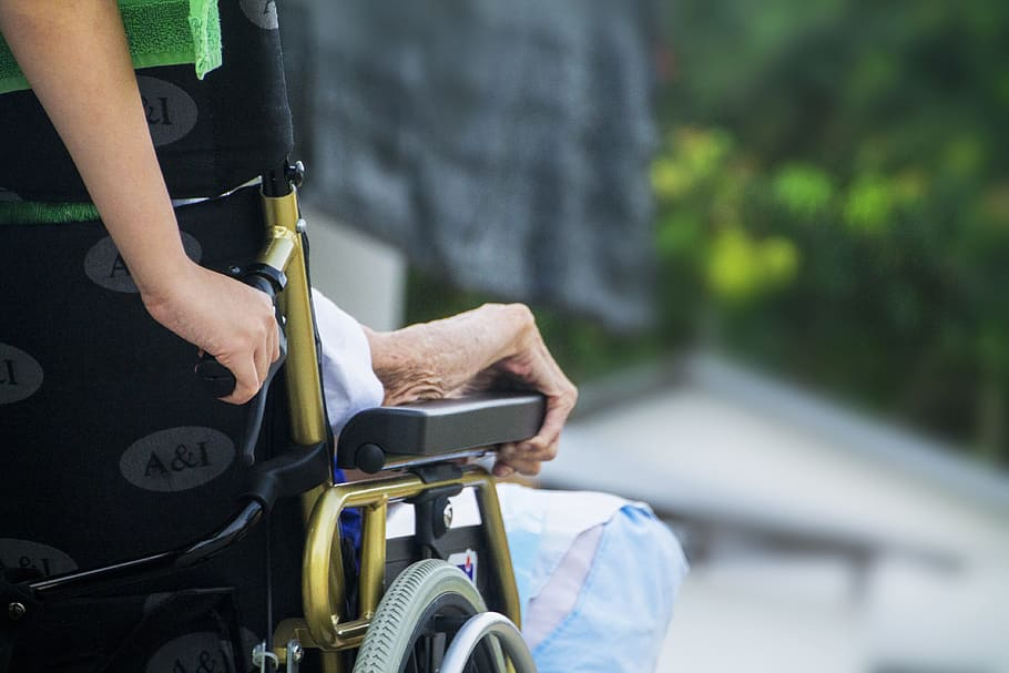 Aged care worker pushing wheelchair